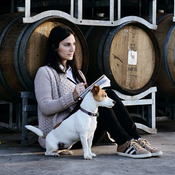 Samantha Jesrati, MD of Levantine Hill sits beside Oak barrels in contemplation with her Jack Russel dog