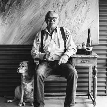 Winemaker Duke Ranson and his dog Cindy sit with some wine at the cellar door in Porungurup in Western Australia