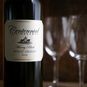Bottle of Centennial Vineyards 2019 Pinot Grigio with wine glasses in background